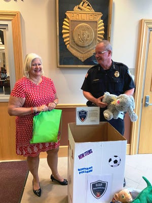 Jude Seppa of D'Ambrosio Eye Care presents Gardner Police Chief Richard Braks with some of the toys donated through the company's Emergency Caring Officer Package program in 2019. [TGN file photo]