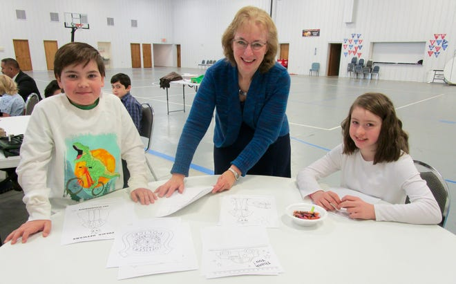 """Reid Kalapp, left; Ramona VanLoo and Teanna VanLoo choose pictures for the Geneseo First Baptist Church children's Sunday school classes to color prior to taking them to the Geneseo Police Station to honor """"Hometown Heroes."""""""