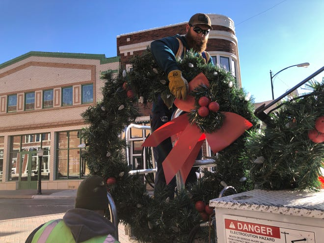 Mike Bliss, left, and Brayden Dreher, right, with the City of Hays, on Monday removed the seasonal holiday wreath decorations from the light poles on Main Street.