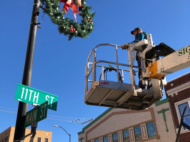 Working from a cherry picker, city of Hays employee Brayden Dreher on Monday prepared to  uninstall a seasonal holiday wreath from the light pole at 11th and Main streets.
