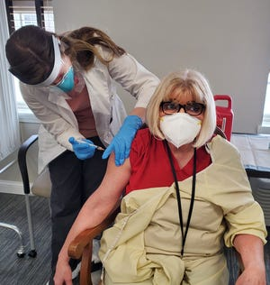 Debbie Yates, right, a nurse at Liberty Village gets her COVID-19 vaccination from a CVS technician on Saturday, Jan. 2, 2021, at Liberty Village in Freeport.