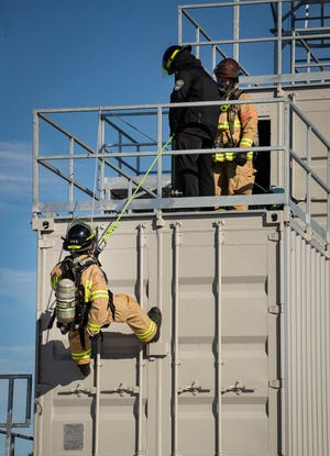 Lakeland firefighters practice a building escape during the grand opening of the Lakeland Fire Department's new training center on Monday in North Lakeland near Tigertown.