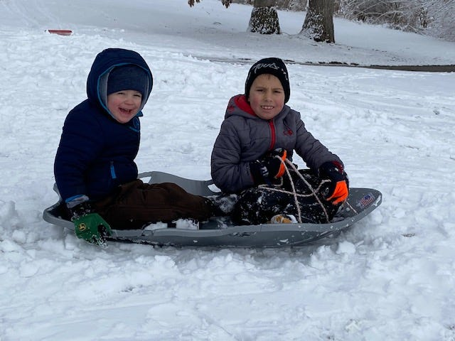 Cousins Tate Sheley and Easton Conrady, both of Lincoln, enjoy sledding down the hill at the Lincoln Elks Sunday near the 18th hole.