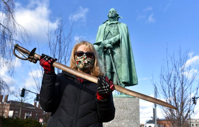 Cindy Gaylord, chairwoman of the Westfield Historical Commission, holds the original sword from the statue of Gen. William Shepard that stands near the town green in the center of Westfield, Mass., on Dec. 29, 2020. [Don Treeger/The Republican via AP]