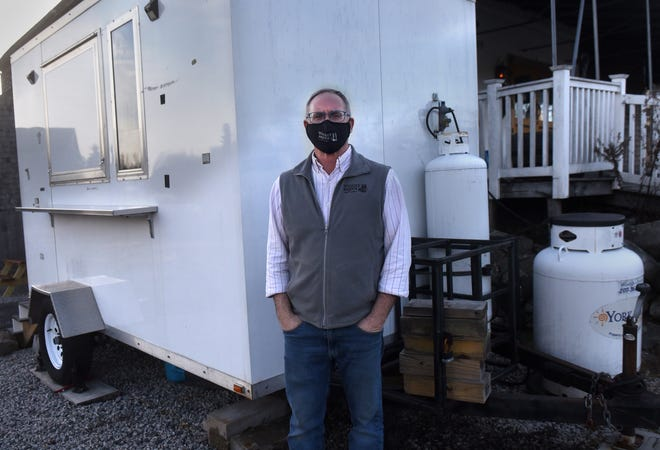 Dave Woods of Wiggly Bridge Distillery in York, Maine, pictured here in January 2021, has used an outdoor mobile kitchen during nice weather.
