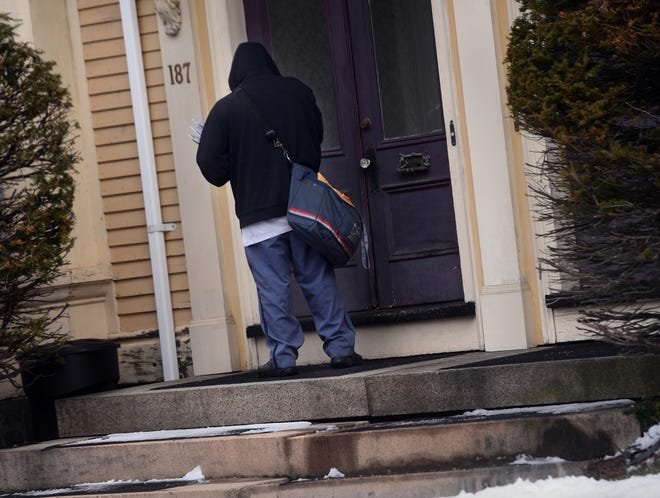 A U.S. Postal Service mail carrier makes deliveries on Central Avenue in Dover on Monday, Jan. 4, 2021.
