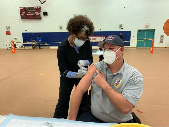 Darcel Spragley, a registered nurse at Kenner Army Health Clinic, administers the first COVID-19 vaccination on Fort Lee to Neal Hudgins, a captain with the post's Fire and Emergency Services, at the post's Clarke Fitness Center Monday, Jan. 4, 2021. The clinic's commander says she hopes to have the first wave of the vaccines administered by the end of the month.