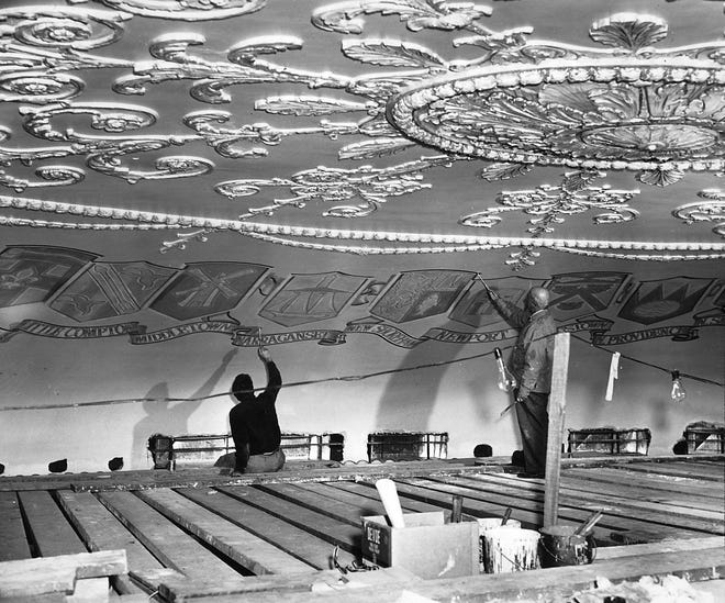 Mural artists Robert Haun, left, and George DeFelice work on the city and town emblems around the dome of Vets Auditorium in the late 1940s. The emblems were painted in DeFelice's studio and then attached to the dome.