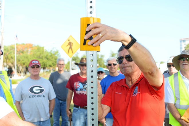"""In May 2016, Venice Mayor John Holic installs an """"A"""" zone tag at a stop sign at the intersection of West Venice Avenue and Tarpon Center Drive. The zone tags help residents identify a flood-prone area."""