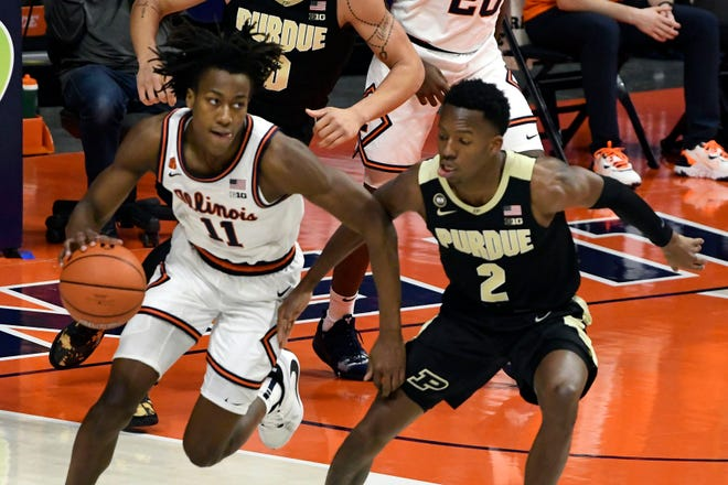 Illinois guard Ayo Dosunmu powers past Purdue guard Eric Hunter Jr. in the first half Saturday in Champaign. [HOLLY HART/THE ASSOCIATED PRESS]