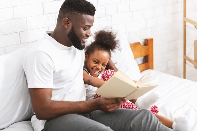 Stock image of parent reading to his child.