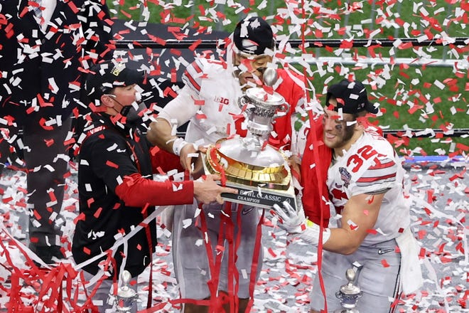 Ohio State head coach Ryan Day, from left, quarterback Justin Fields and linebacker Tuf Borland hold up the trophy after their win against Clemson in the Sugar Bowl NCAA college football game Friday, Jan. 1, 2021, in New Orleans. Ohio State won 49-28.