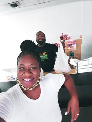 Atiba Johnson, co-owner of Front Street Market & Produce, posed with Wilmington business owner Neeka Wrice (left)   during the opening of his market.