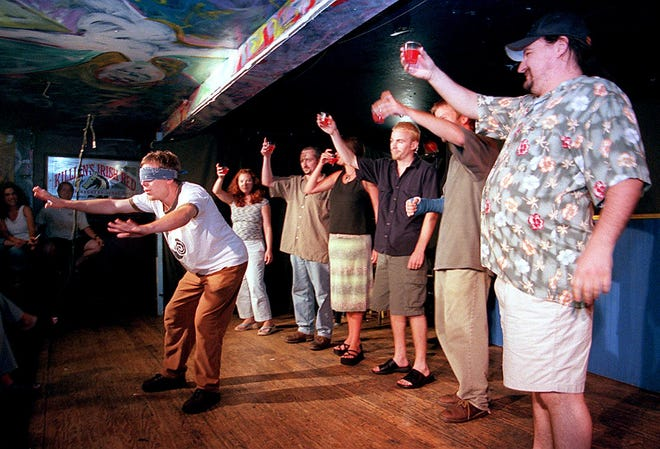 Members of The Changing Channels comedy troupe drink a toast to the blindfolded Chris Hendricks at the start of their weekly show at Bessie's in Wilmington in the early 2000s.