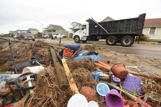 Crews and residence continue to clean up  along East Beach Drive Thursday August 20, 2020, after Hurricane Isaias in Oak Island, N.C.