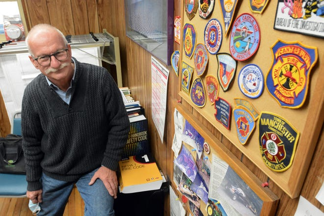 Paul Yellen, Plainfield fire marshal, with some of the fire department patches he has collected over the past 33 years. He plans to retire Feb. 4.
