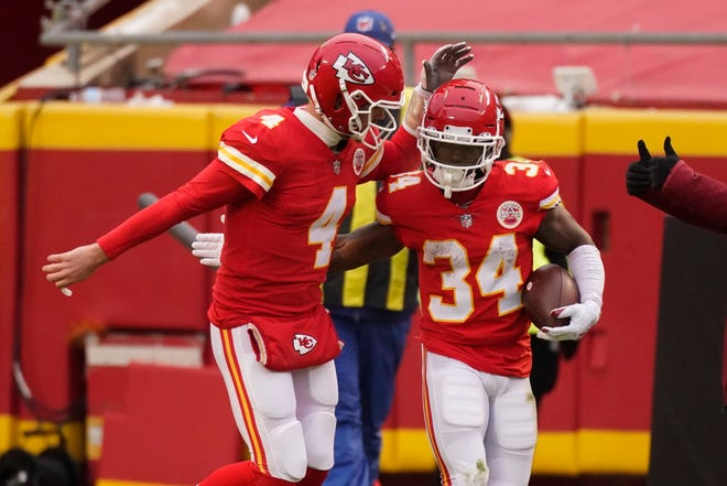 Kansas City Chiefs running back Darwin Thompson (34) celebrates with quarterback Chad Henne (4) after scoring on a 1-yard touchdown run during the first half of an NFL football game against the Los Angeles Chargers on Sunday in Kansas City.
