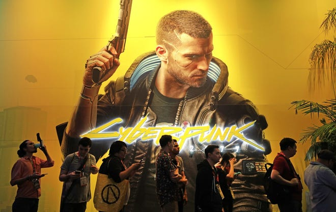 """Attendees wait in line June 11, 2019 for a peek at """"Cyberpunk 2077"""" from CD Projekt Red during E3 at the Los Angeles Convention Center."""