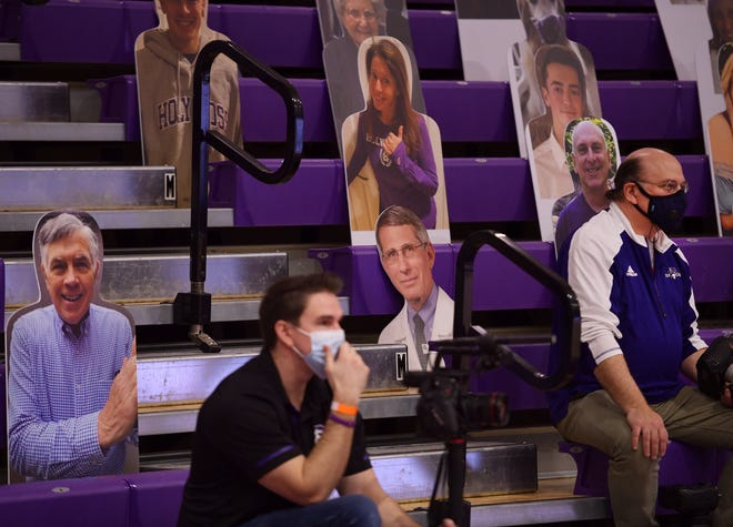 Photographers sit among cardboard cutouts in the bleachers behind each basket at the Hart Center on Monday. The cutouts included alumnus Dr. Anthony Fauci.