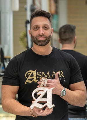 Jewelry designer Asmar Akman holds one of his creations