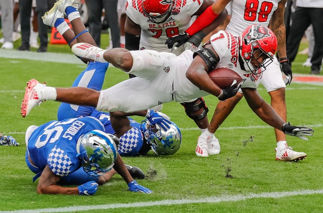 NC State Wolfpack running back Zonovan Knight (7) dives for a touchdown over Kentucky Wildcats defensive back Brandin Echols (26) during the second half of Saturday's Gator Bowl. Knight finished with 52 rushing yards and a touchdown on 12 carries.