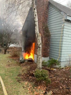 Flames show next to the chimney of a home on Bow Street in Stoneham that was damaged by a fire on New Year's Eve.