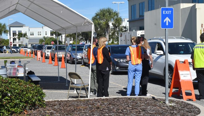 Drivers with appointments wait in line Monday, as the Florida Department of Health staff began offering drive-through COVID-19 vaccinations at the DOH's Viera complex. The Moderna vaccine is available for ages 65 and older, and health care workers who provide direct patient care, but who are not associated with a hospital system.