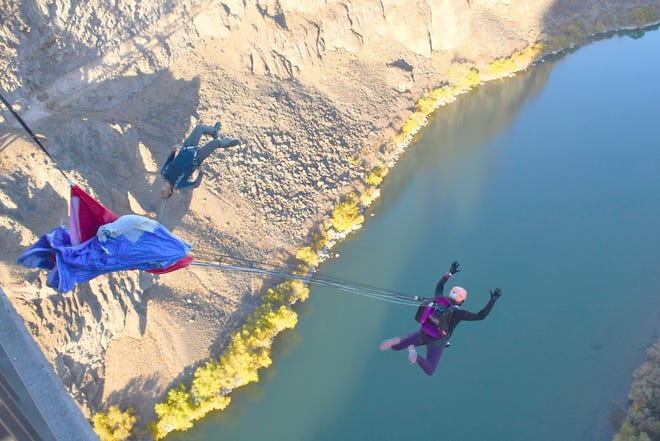 Nicole Senecal, a Burlington athlete and business owner, right, parachutes from the Perrine Bridge, 486 feet above the Snake River Canyon in Twin Falls, Idaho on Oct. 23, 2020. Her companion jumper, Kyle Miller, executes a gainer before deploying his canopy. Senecal, 37, set a Guinness World Record that day with 37 consecutive parachute jumps (and return climbs) from a fixed point in a 12-hour period.