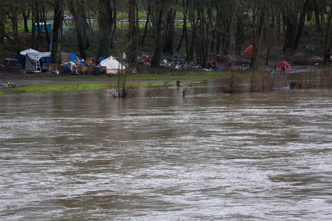 The Willamette River rises near an encampment in Wallace Marine Park last week.