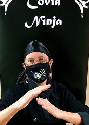 """Jodi Williams, director of behavioral health at the Flandreau Santee Sioux Health Clinic, poses in front of a """"Covid Ninja"""" poster to symbolize the work she and other healthcare workers have done during the pandemic."""