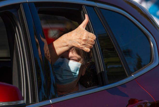 """Debbie Hayner, 76, of Palm City, Fla., gives a thumbs-up after receiving the Moderna COVID-19 vaccine during a COVID-19 drive-thru vaccine clinic held by the Florida Department of Health's Martin County office on Monday, Jan. 4, 2021, in Stuart. """"The shot was a breeze,"""" Hayner said."""