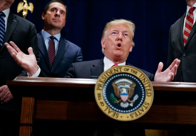 FILE - In this Oct. 19, 2018 file photo, President Donald Trump speaks during a ceremony as Rep. Devin Nunes, R-Calif. looks on.