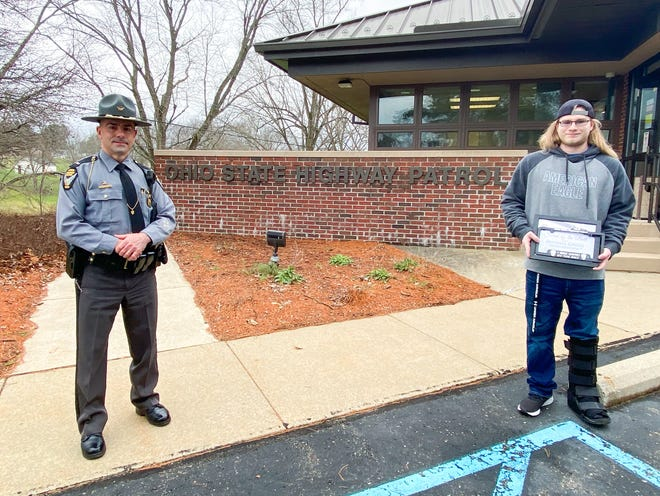 Lt. Russell Pasqualetti honors Michael Grigg with the Saved by the Belt Award at the Zanesville post of the Ohio State Highway Patrol Monday afternoon.