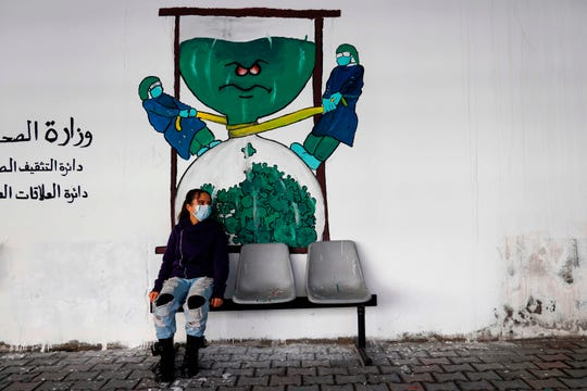 A Palestinian child sits beneath graffiti depicting medical workers fighting the COVID-19 virus outside the Health Ministry in Gaza City on Dec. 20, 2020.