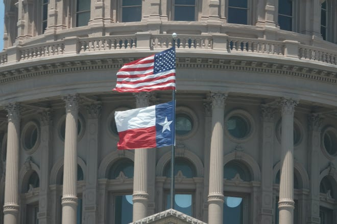 U.S. and Texas flags flying at Texas Capitol. KEN HERMAN/American-Statesman