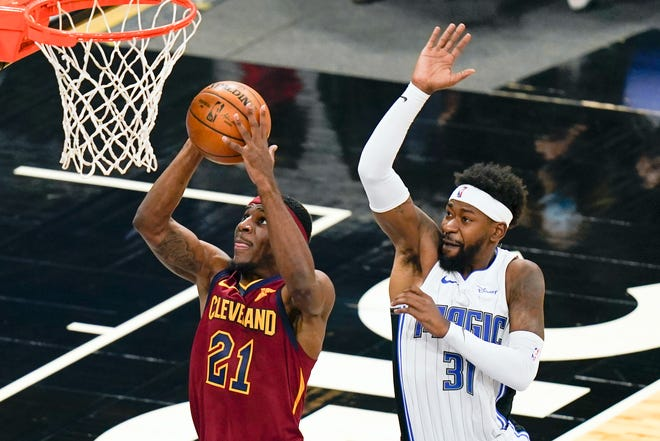 Cleveland Cavaliers guard Damyean Dotson (21) is fouled by Orlando Magic guard Terrence Ross (31) as he goes up for a shot during the second half of an NBA basketball game, Monday, Jan. 4, 2021, in Orlando, Fla. (AP Photo/John Raoux)