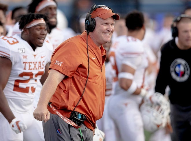 Texas assistant coach Herb Hand smiles after offensive lineman Samuel Cosmi (52) scored a touchdown on Oct. 5, 2019, in Morgantown, W. Va. [NICK WAGNER/AMERICAN-STATESMAN]