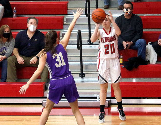 Loudonville's Shalen Guilliams (20) puts up a 3-point shot over North Royalton's Kaitlyn Bockelman during high school girls basketball action on Monday at Loudonville High School. The Redbirds won, 66-45.