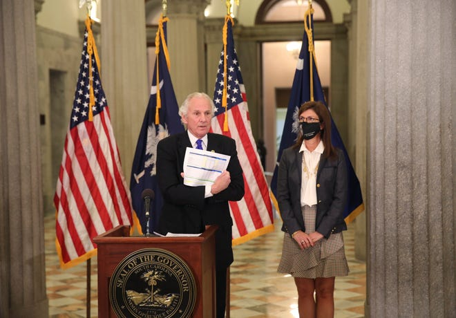 Gov. Henry McMaster shows a listing of hospitals in the state that have received the COVID-19 vaccine during a news conference at the Statehouse in Columbia on Tuesday. McMaster wants health officials to set a Jan. 15 deadline to get vaccines before they open them to frontline workers and people over age 75.