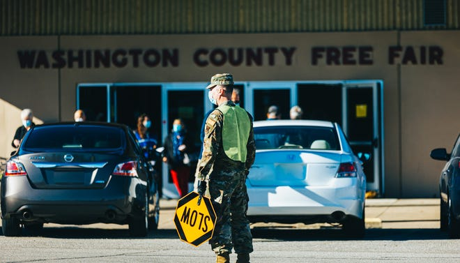 National Guard members help direct traffic while the first public vaccines were administered Tuesday, Jan. 5, at the Washington County Fairgrounds in Dewey.