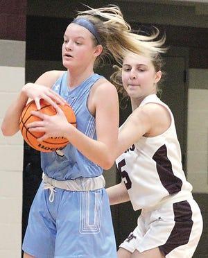 Bartlesville High School's Jordan Bilger, left, plays keep away from a Jenks High player during varsity girls basketball action in December.