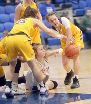 Pilot Grove's Emma Sleeper (12) and Natalie Glenn (25) battle New Franklin's Abby Maupin (23)for the ball in the second half Monday night in the opening round of the New Franklin Tournament.