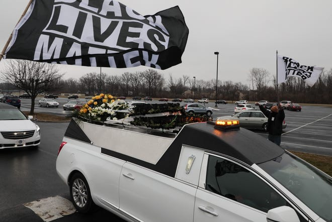 Mourners wave Black Lives Matter flags as the hearse carrying Andre' Maurice Hill leaves the First Church of God following his funeral on Tuesday, Jan. 5, 2021 at First Church of God.
