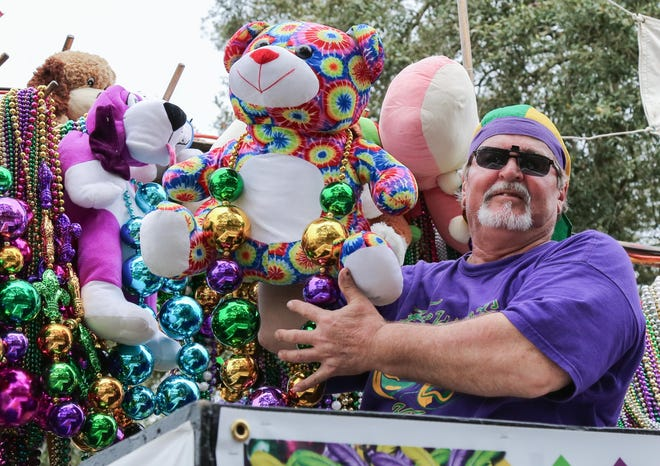 A member of the Krewe of Cleophas prepares to toss a stuffed animal to the waiting crowd during the Carnival club's 2020 parade in Thibodaux.