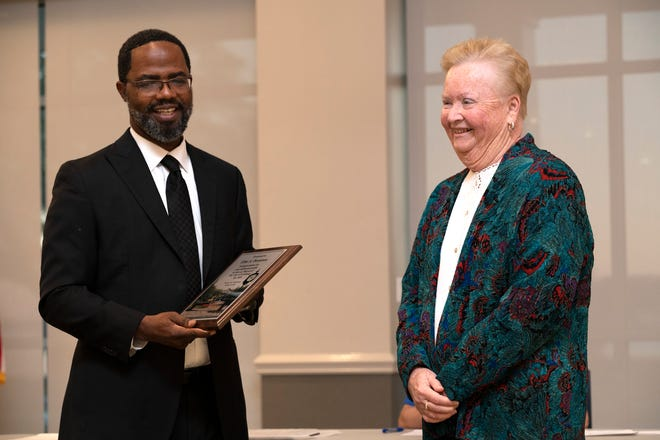 New mayor John Christian presents former mayor Elise Dennison with a plaque for his eight years on the city commission on Monday night. [Cindy Peterson/Correspondent]