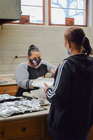 Lakeidra Johnson, left, and Jenny Stephenson fill Styrofoam boxes with food at the Feed My People food distribution center. Johnson has been the director of the program for 18 years and is relying on donations to update their kitchen and plumbing.