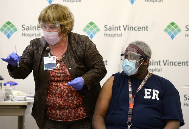 Sallie Piazza, R.N., chief nursing officer at Saint Vincent Hospital, administers the first of the hospital's COVID-19 vaccinations to Herman Brown, an emergency department customer service liaison, on Dec. 17. Saint Vincent employees began receiving second doses of the vaccine on Monday.