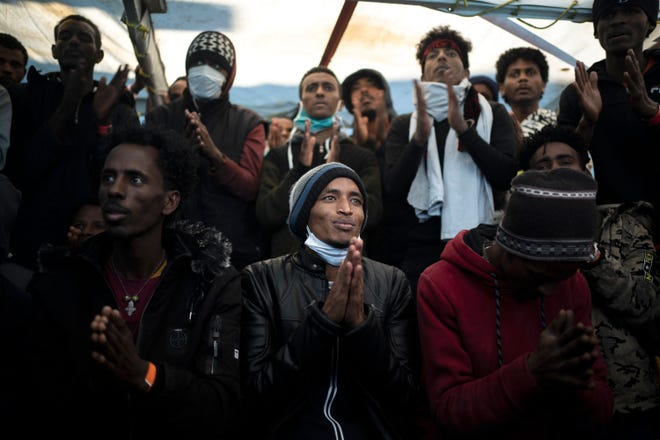 Yohaness, from Eritrea, prays with other migrants as they arrive at the coast of Italy on board the Spanish NGO Open Arms vessel after being rescued in the Mediterranean sea, about 8 miles south Italy on Monday, Jan. 4, 2021. Italy has allowed a Spanish-flagged charity ship with 265 rescued migrants aboard to anchor off Sicily on Monday. (AP Photo/Joan Mateu)
