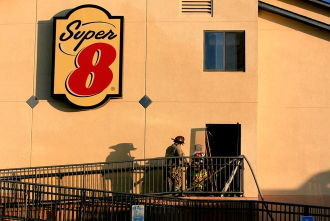 Hutchinson Fire Department firefighters begin to remove tools after putting out a fire Tuesday morning on the south side of the Super 8 Motel. People were evacuated in the early-morning fire, which investigators believe was caused by an electrical short in the wiring in the stairwell.