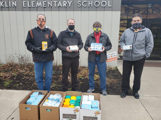 Massillon Lions Club members Rick Dalsky, from left, Jeremy Wagner and President Bryan Corban presented disposable face masks and sanitizing wipes to Franklin Elementary School Principal Mike Medure. The club collected the donations as part of a service project.